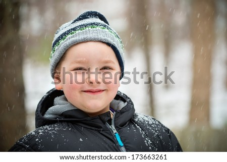 Happy child in the snow on winter day - stock photo
