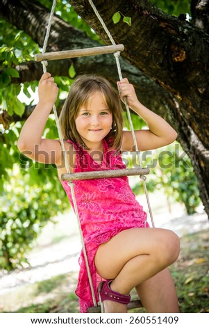 Happy child is playing on rope ladder outside in nature - stock photo