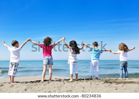 happy child kids have fun and play games on beach
