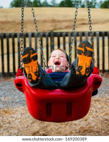 Happy child laughing while swinging at playground - stock photo