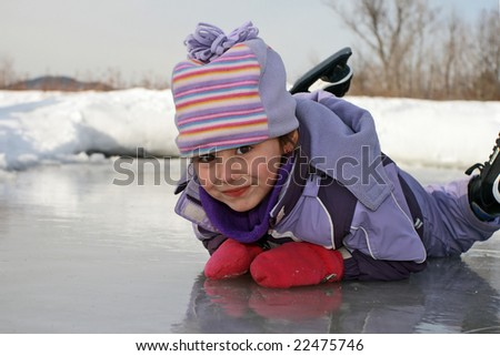 Happy child laying on skating rink ice surface during winter. - stock photo
