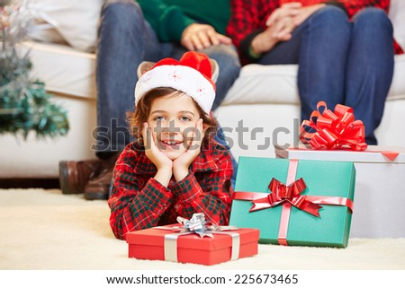 Happy child laying with gifts at christmas eve on the floor - stock photo
