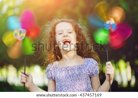 Happy child leisure in summer outdoor. Laughing girl holding a rainbow pinwheel toys.