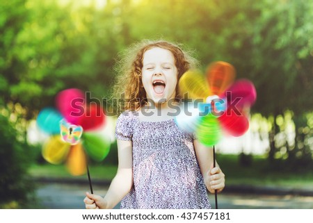 Happy child leisure in summer outdoor. Laughing girl holding a rainbow pinwheel toys. - stock photo