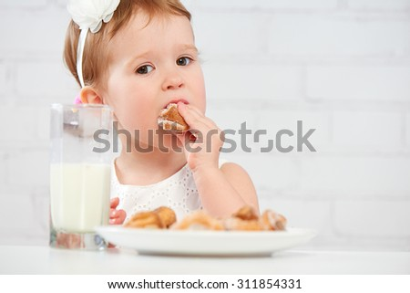 happy child little girl eats cookies and milk