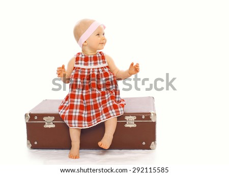 Happy child little girl in dress sitting on the suitcase playing and having fun - stock photo