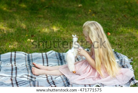 Happy child. Little girl play with toy on grass;