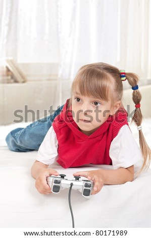 Happy child - little girl playing a video game - stock photo