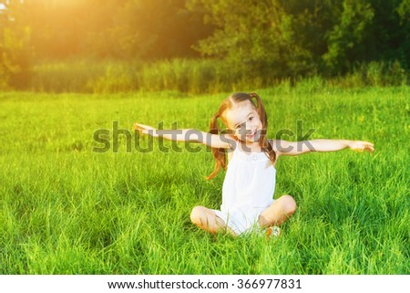 happy child little girl spread his arms in a white dress lying on the grass Summer - stock photo
