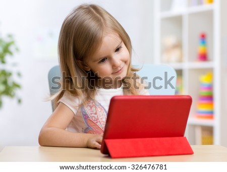 happy child little girl using tablet computer sitting at table - stock photo