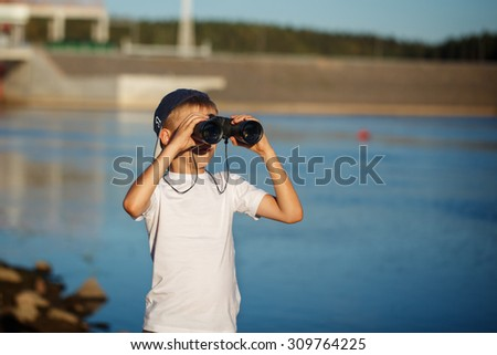 Happy child looking in nautical binoculars  against blue water background. Kid having fun on nature. Summer sea dream and imagination. Adventure and travel concept - stock photo