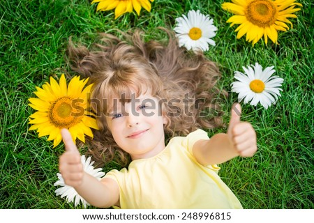 Happy child lying on grass. Funny kid playing in park. Beautiful spring flowers. Unusual top view portrait. Success and winner. Thumbs up. Like - stock photo