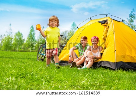 Happy child on a bike hiking journey with cup very happy running with cup - stock photo