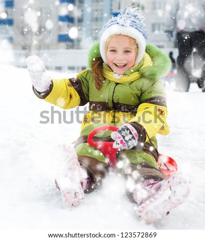Happy child on sledge in winter - stock photo