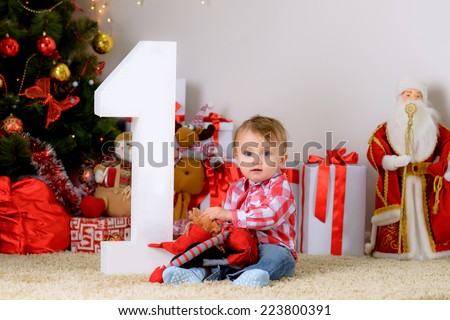 happy child on the floor under the tree with a new toy is celebrating its first Christmas and New Year - stock photo