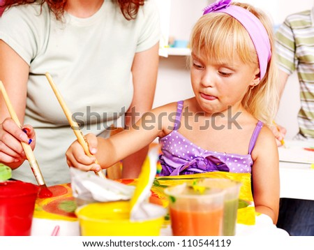 Happy child painting at easel in school. Education. - stock photo