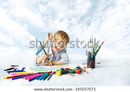 Happy child painting with brush in album using a lot of drawing tools. Creativity and education concept. - stock photo