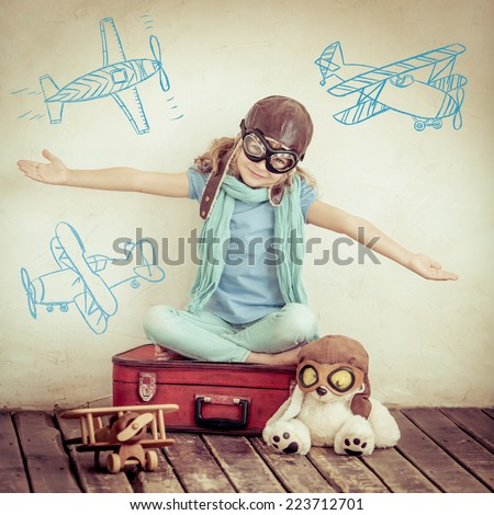 Happy child pilot with vintage toys. Kid playing with wooden airplane at home. Adventure and travel concept. Retro toned - stock photo