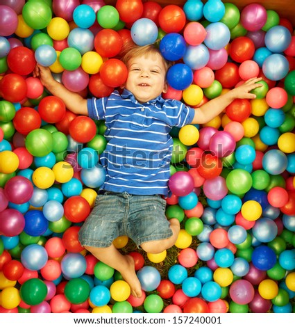 Happy child playing at colorful plastic balls playground high view - stock photo