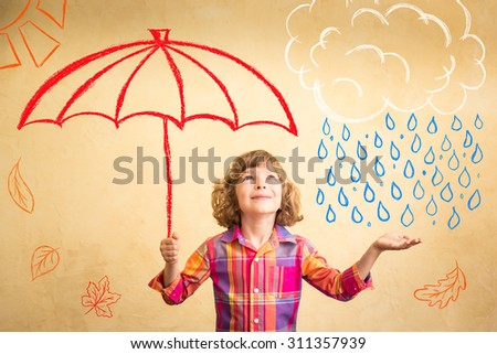 Happy child playing at home. Drawing autumn theme. Imagination and freedom concept - stock photo