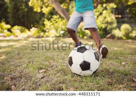 happy child playing football at park