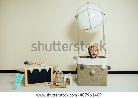 Happy child playing in handmade basket of air balloon. Kid having fun at home. Young pilot indoors at solid color background with copy space. Boy in hat like a helmet looking away. Blank chalkboard. - stock photo