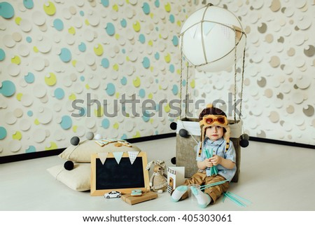 Happy child playing near handmade basket of air balloon. Kid having fun at home. Young pilot indoors at fun background. Boy looking at camera.  Copy space - stock photo