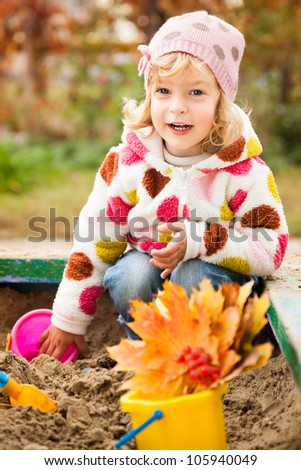 Happy child playing on playground in autumn park. Healthy lifestyles concept