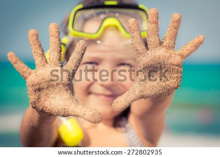 Happy child playing on the beach. Kid showing sand on hands. Summer vacations concept - stock photo