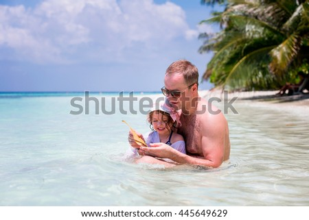 Happy child playing together with father in blue ocean in a tropical resort. Paradise landscape, turquoise water, coconut palms, white sand. Summer vacations. Family having fun catching crab