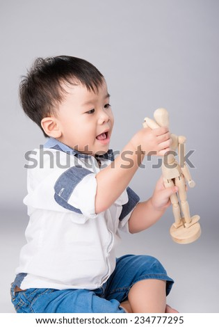 Happy child playing with a wooden man. Cheerful boy smiling - stock photo