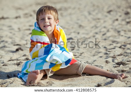 Happy child playing with sand at the beach in summer