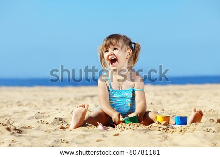 Happy child playing with sand at the beach in summer - stock photo