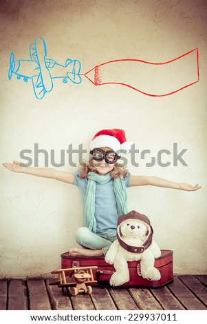 Happy child playing with toy airplane at home. Kid dressed in pilot against drawn plane on grunge wall background. Christmas holiday. Retro toned - stock photo