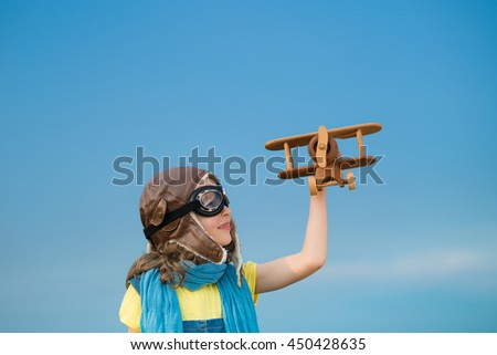 Happy child playing with toy airplane outdoors. Kid having fun against summer sky background. Travel and imagination concept