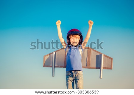Happy child playing with toy wings against summer sky background - stock photo