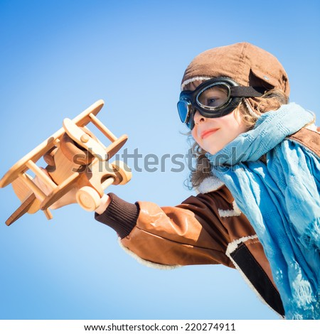 Happy child playing with toy wooden airplane against winter sky background