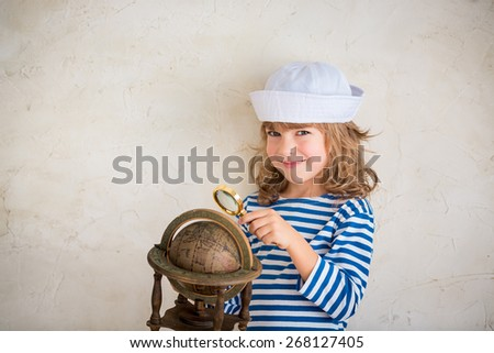 Happy child playing with vintage nautical things. Kid having fun at home. Summer sea dream and imagination. Adventure and travel concept - stock photo