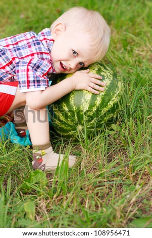 Happy child playing with watermelon outdoors in summer nature - stock photo