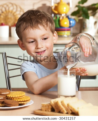 Happy child pours milk from jug - stock photo