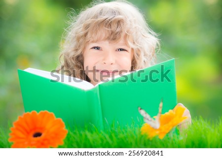 Happy child reading book against green spring blurred background. Ecology concept - stock photo