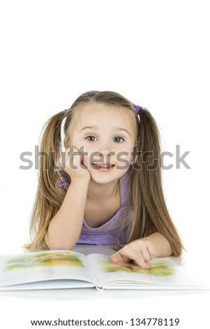 happy child reading book on the floor isolated on white background with copy space - education concept - stock photo