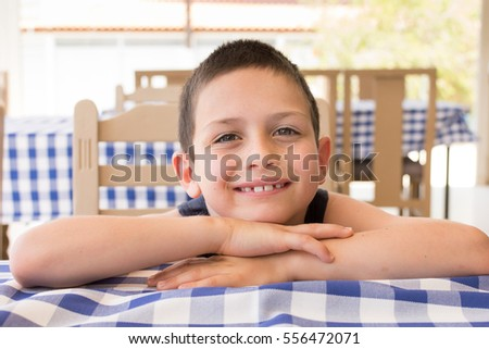 Happy child resting on table in cafe dining restaurant.