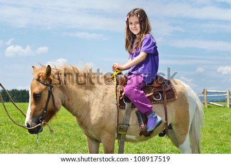 happy child ride farm animal brown pony with blue sky in background and beautiful nature - stock photo