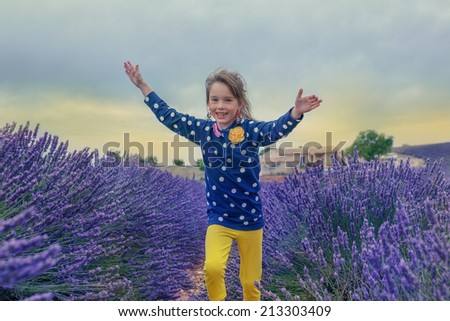 Happy child running along lavender farmland - stock photo