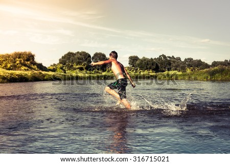 Happy child running towards sunset on river shore  - stock photo