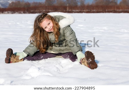 Happy child sit down in the snow - stock photo