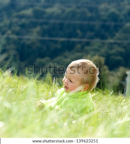 Happy child sitting in the grass - stock photo