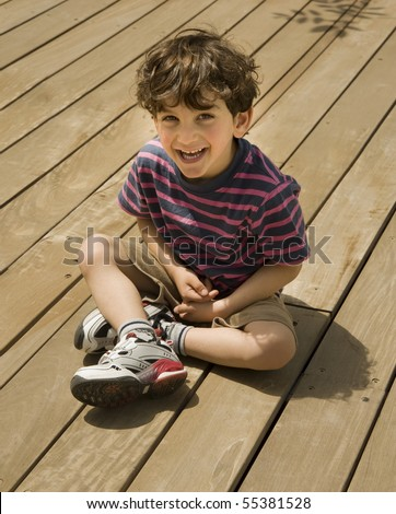 happy child sitting on a woden deck - stock photo