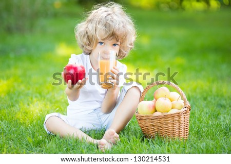 Happy child sitting on green grass and drinking apple juice in spring park. Healthy eating concept - stock photo